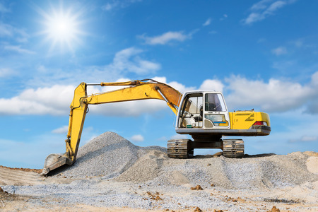 mound: Excavator parked on the mound with sunlight and blue sky background.