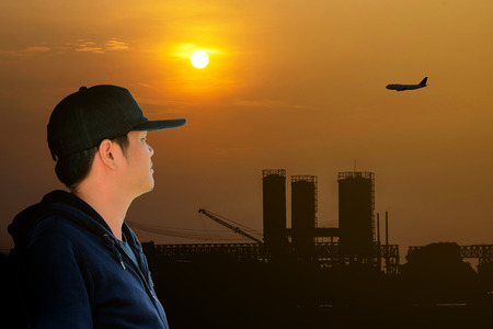 long sleeve shirt: Asian man wearing a blue long sleeve shirt and wearing a hat looking at the airplane flying over the factory on the red sky with beautiful sunlight. Stock Photo