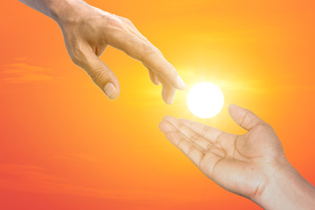 toward: Two hands are extended toward each represents an assist each with beautiful sunlight background.