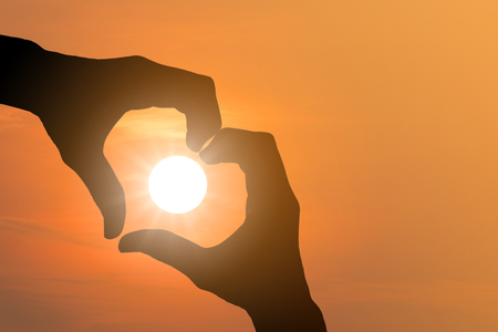 heart symbol: Silhouette of hand made heart symbol across the sun was falling. Stock Photo