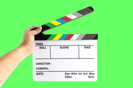 directors cut: Mens hand holding camera slate  for the filming isolated on green background.