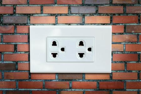 wall plug: AC power plug on the vintage brick wall.