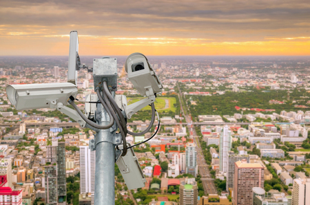 close circuit camera: CCTV or surveillance camera  recording  important events and a guard house and property with the sunrise in the morning at the big city background. Stock Photo
