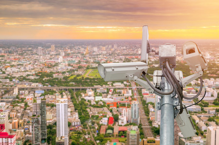 city surveillance: CCTV or surveillance camera  recording  important events and a guard house and property with the sunrise in the morning at the big city background. Stock Photo