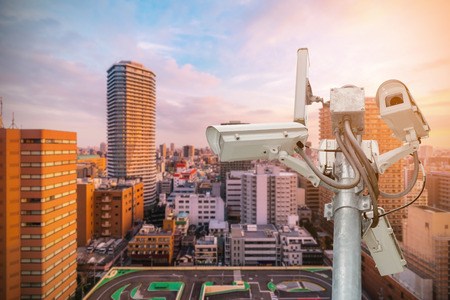 guard house: CCTV or surveillance camera  recording  important events and a guard house and property with the sunrise in the morning at the big city background. Stock Photo