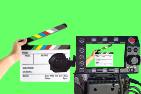 focus on background: LCD monitor on the camera focus at a hand holding camera slate  for the filming isolated on green background.