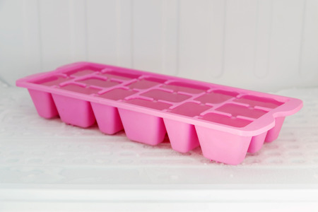 Colorful plastic ice tray in the freezer compartment of the refrigerator. Stock Photo