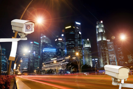 city surveillance: Closeup of traffic security camera surveillance (CCTV) on the road in the night city. Stock Photo
