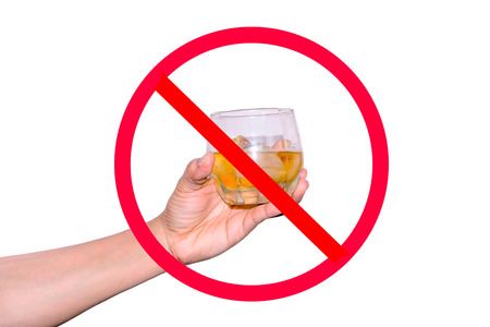 ices: The red circle with slash on womans hand holding a glass of wine with ices on white background; concept for stop drinking. Stock Photo