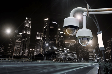 Closeup CCTV camera outdoors with colorful night cityscape background.