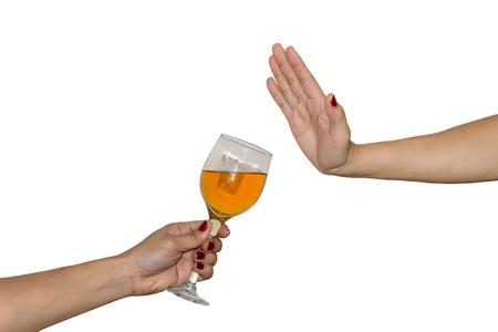 alcoholismo: vidrio mano extendida bebida de alcohol de la mujer por el contrario rechazada en el fondo blanco. concepto para no beber y conducir. Foto de archivo