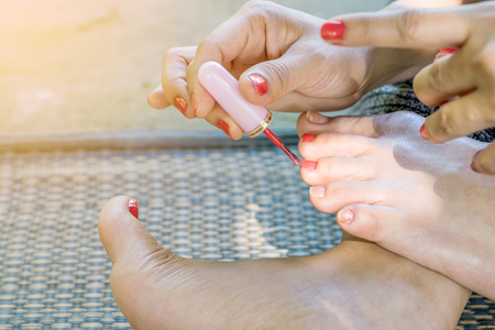 painted toenails: Young women are painted toenails with red nail polish.