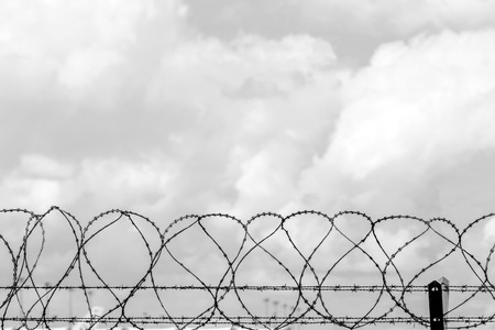 prison yard: Closeup fence barbed wire with clouds sky background. Stock Photo