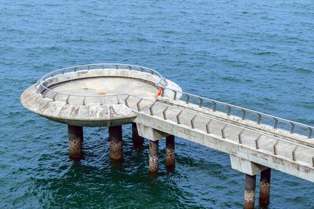 extending: Concrete bridge pier extending into the sea.