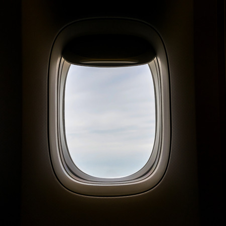 looking through an object: Closeup of the airplane window with the clouds sky background.