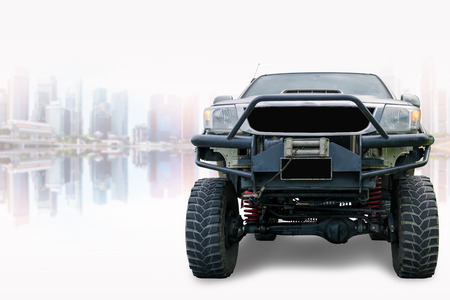 Closeup front of off road truck with beautiful cityscape background.