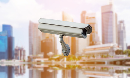 CCTV security camera isolated on blurred cityscape background.