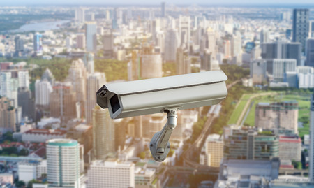 electronic survey: CCTV security camera isolated on blurred cityscape background.