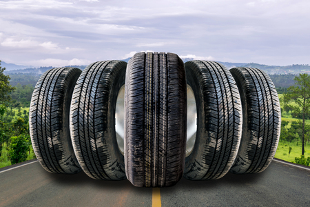 Car tires in row on the street with the forest background.