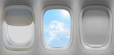 Closeup group of the airplane windows with the clouds sky background. Stock Photo
