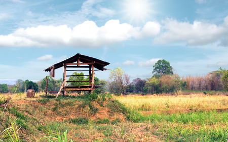 Vintage wooden cottage in the farm with beautiful sunlight and cloudsky. Stock Photo