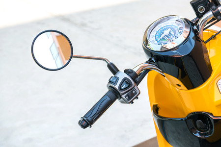 throttle: Closeup to handle,speedometer and rear view mirror of the motorcycle.