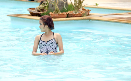 looked: The girl was walking in the pool crystal clear and blue that looked cool and comfortable. Stock Photo
