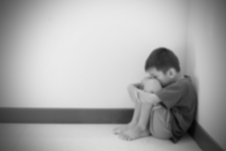 hugged: Blurred of the boy hugged her knees in tears in a corner of the room, black and white tone.