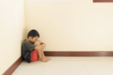 hugged: Blurred of the boy hugged her knees in tears in a corner of the room.