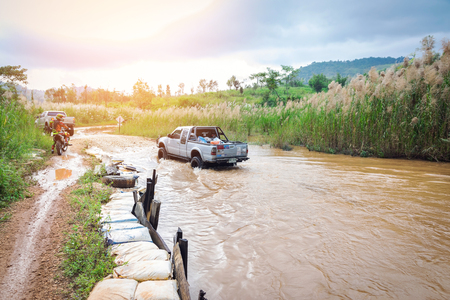 Ratchaburi,Thailand -Dec 4,2016: Four-wheel drive pickup truck were wading across the river in the forest. Editorial
