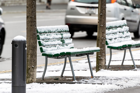Empty chairs covered with snow in winter, on a side street in the city of Lucerne.