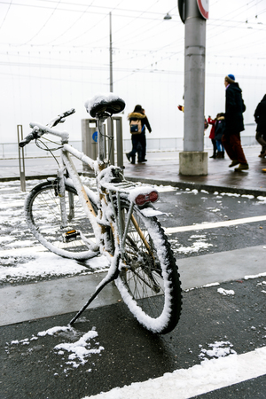 winter tires: The bicycle parked on the road is covered with snow in winter in Switzerland.