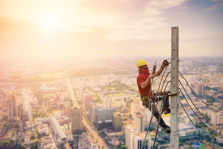 전기 기사들은 전력선을 설치하기 위해 전기 기둥을 등반하고 있습니다.