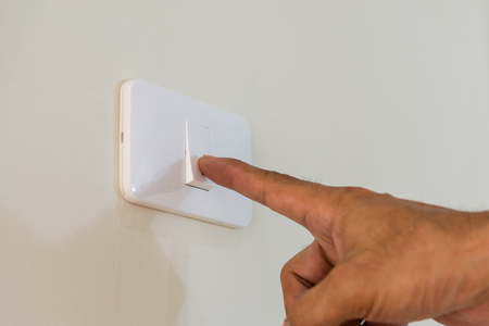 mounted: Mens fingers are extended to open the light switch on the wall.