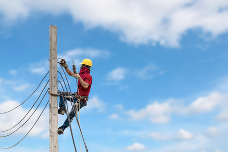 Electricians are climbing on electric poles to install power lines. Stock Photo