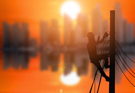 Schattenbild eines Elektrikers klettern auf elektrische Pfosten, um Stromleitungen mit dem schönen Sonnenuntergang am Stadthintergrund zu installieren.
