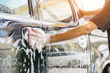 Auto service staff cleaning a car with sponge and car wash-car detailing and valeting concepts.