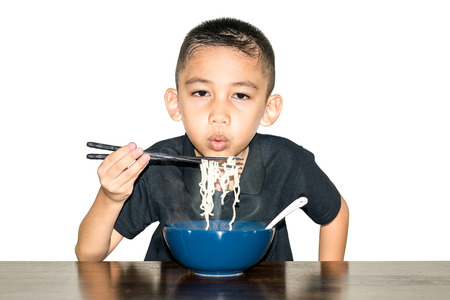 Asian boy wearing a black shirt is using chopsticks, noodles in a blue ceramic cup and cooled to eat-Fast food & Beverage concepts.