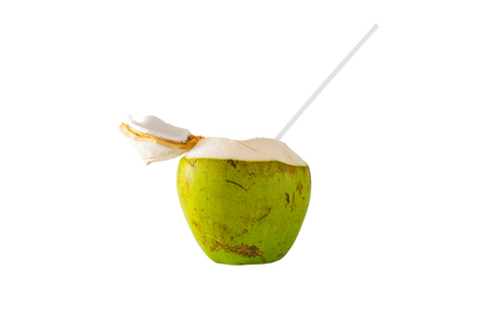 Coconut is pierced with a tube to absorb water isolated on white background, with clipping path. Stock Photo