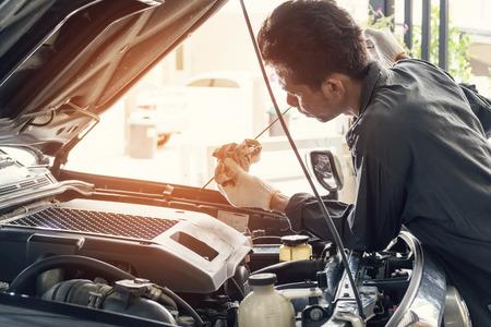 Mechanik samochodowy w szarym mundurze sprawdza poziom oleju silnikowego, koncepcję przemysłu motoryzacyjnego i garażu.