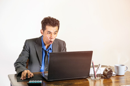 A young businessman wearing a suit was shocked when he looked at a laptop on a desk in his office, business people concept. Reklamní fotografie