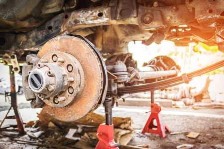 Old and rusty cars suspension, which removes the wheels for repair, replacement and change news parts -Automotive industry and garage concepts. Stock Photo