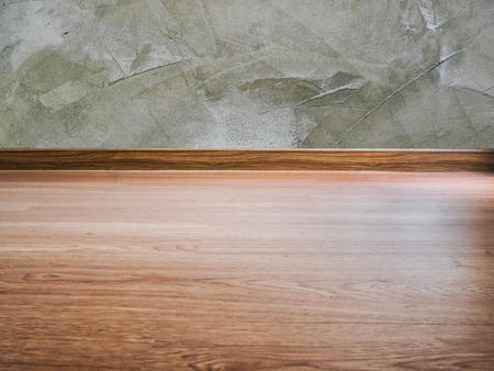 Laminate flooring and teak wood edges and cement wall-with copy space.