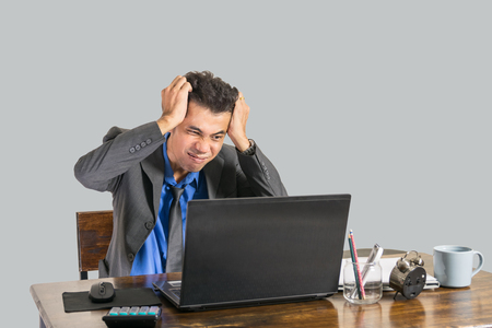 A young businessman wearing a suit was shocked when he looked at a laptop on a desk in his office, business people concept. Foto de archivo