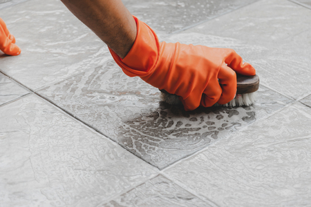 Hand of man wearing orange rubber gloves is used to convert scrub cleaning on the tile floor. Stock Photo