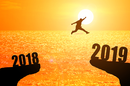 Silhouette of young man jumping between 2018 and 2019 years with beautiful sunset at the sea-concepts of news year and business target. Stock Photo