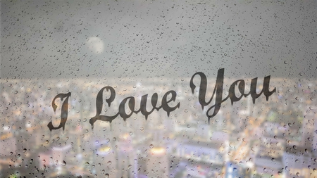 Draw letters I love you by hand on a glass with water drops droplets with night cityscape background. Stock Photo