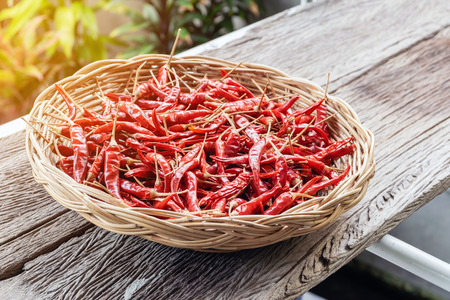 Close-up group of red dried peppers in a wicker basket. Stock Photo