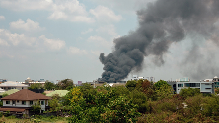 Black smoke groups caused by fire that is burning buildings or houses.