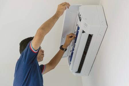 Air conditioner repairers in blue uniform are checking and repair air hanging on the wall.